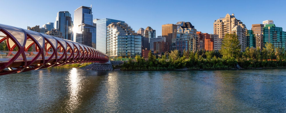 Peace Bridge across Bow River during a vibrant summer sunrise. Taken in Calgary, Alberta, Canada.